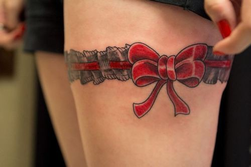 Red_bow garter tattoo on upper leg